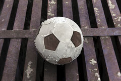 Old football ball on rust iron bar Royalty Free Stock Photography