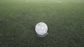 Old football on the fake grass Royalty Free Stock Photos