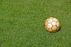 Old football  and fresh spring green grass. Football lying on the grass Stock Photo