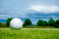 Old football on green grass in Stadium Stock Images