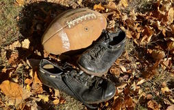 Old football memories. A pair of spiked shoes and an old leather pigskin football bring back memories the football player Stock Photography