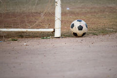 Old football put near the goal post Royalty Free Stock Photography