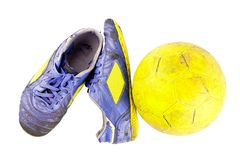 Old football shoes damaged and old dirty yellow futsal ball on white background football object isolated