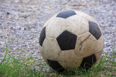 An old football or soccer ball on crushed gravel yard Royalty Free Stock Photography