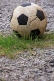 An old football or soccer ball on crushed gravel yard Royalty Free Stock Image