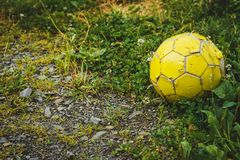 Old football or soccer ball on crushed gravel yard Royalty Free Stock Image