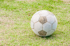 Old football, soccer ball on the grass Royalty Free Stock Image