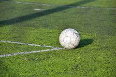 Old football, soccer ball on the grass Royalty Free Stock Photo