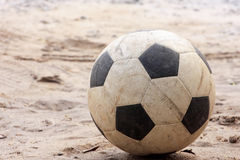 An old football or soccer ball on sand.  Stock Photography