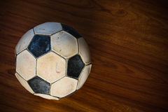 Old football on wooden background, popular sport of the world, sport background and empty area for text, damaged ball on wooden Stock Photos