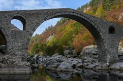 Old footbridge made of stone locks. Devil bridge landmark in Rhodopes mountain, Bulgaria against colorful autumnal forest and blue sky Royalty Free Stock Images