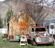 Vintage Shell gas sign in front of vintage Ford truck. This old Ford vintage pick up truck is parked in front of a rustic looking wood shed that has a retro stock photos