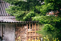 Old forest hunter`s house with harvested wood. Royalty Free Stock Images