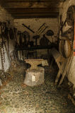 Old forge with rusty anvil. Stock Photos