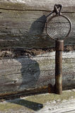 Old Forged Key On The Log-house Wall. Old forged key on the nail in the wall of the village log-house Royalty Free Stock Photos