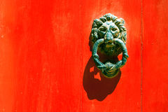 Old forged maltese handle  on the red door. Old forged maltese handle  in the form of a lion`s head  on the red door Stock Images