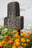 Cross with flowers. Old and forgotten cross gravestone with flowers growing Royalty Free Stock Image
