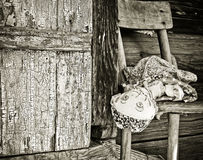 Old Forgotten Doll. Old forgotten hand-made doll at wooden textured door stock photography