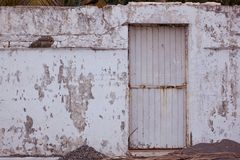 Old and forgotten wall with a metal door. Antique and wasted wall in an old little town from Mexico stock image