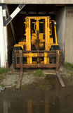 Old Fork Lifter. Old yellow fork lifter truck in a hangar Stock Images