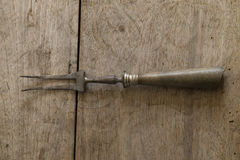 Old rusty meat fork on a brown wooden board Stock Photography