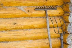 Old forks, rakes. Background - yellow wooden wall made of logs royalty free stock photo