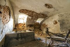 Old forsaken empty basement room of ancient building or palace with cracked plastered brick walls, low arched ceiling, small. Windows with iron bars and dirty royalty free stock photography