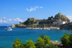 Old Fort Corfu Greece with marina and sailboats. The Old Fort in Kerkira, also known as Corfu Town, on Corfu, Greece towers above a tranquil marina filled with Stock Photo