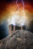 Old fortress. On rock struck by lightning from dark red sky stock photos