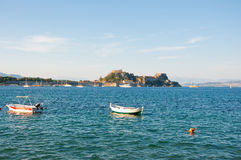 The Old Fortress of Corfu and boats on the water seen from the shore. Greece Royalty Free Stock Image