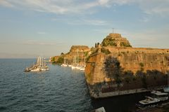 The Old Fortress of Corfu and its yacht marina with rising moon at the background, Kerkyra, Corfu Island, Greece, Europe royalty free stock photo