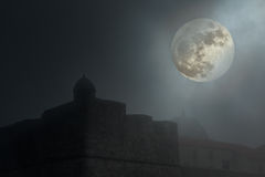 Old fortress in a foggy night. Old european fortress in a foggy full moon night. Added some digital noise stock photo