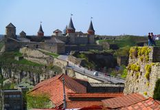Old fortress, Kamenets Podolskiy, Ukraine. View of the old fortress with turkish bridge over canyon and ancient walls overgrown with some yellow flowers in Stock Photography