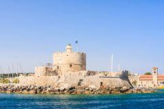 Old fortress with lighthouse. Port of Mandraki. Rhodes Stock Photography