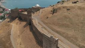 Fortress wall in Sudak. Old fortress ruins and walking tourists stock video footage
