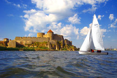 Old fortress and sailboat. Medieval fortress in town Belgorod-Dnestrovskiy (The South of Ukraine). Old name of town is Akkerman. Waves on the Dnestr estuary Stock Photo