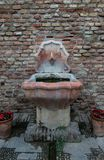 Old fountain in front of a brick wall royalty free stock image