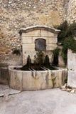 Old fountain in Gigondas. Old stone public fountain in Gigondas, Vaucluse, France royalty free stock photos