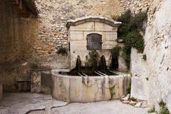 Old fountain in Gigondas. Old stone public fountain in Gigondas, Vaucluse, France stock photo