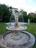 An old fountain with a woman sclupture in a romanian house yard. An old fountain with a woman lighted sclupture in a romanian house yard surounded by grass Stock Image