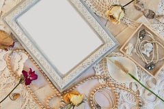 Old frame with beads and with dried roses. Royalty Free Stock Images