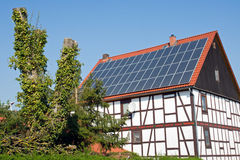 Old frame house with solar cells on the roof Stock Images