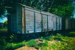 Old freight car abandoned. Old rusty freight car abndoned in out of use tracks near  a train station. the car is surrounded by green trees and has a few Royalty Free Stock Image