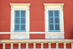 Old french blue shutter windows in red house, Nice, France. Stock Images