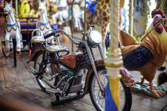 Old French carousel in a holiday park. Bike on traditional fairground vintage . Merry-go-round with . Royalty Free Stock Image