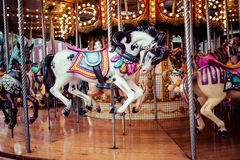 Old French carousel in a holiday park. Three horses and airplane on a traditional fairground vintage carousel. Merry-go-round with. Horses Stock Photo