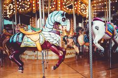 Old French carousel in a holiday park. Three horses and airplane on a traditional fairground vintage carousel. Merry-go-round with Royalty Free Stock Images