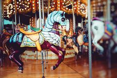 Old French carousel in a holiday park. Three horses and airplane on a traditional fairground vintage carousel. Merry-go-round with Royalty Free Stock Image