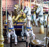 Old French carousel in a holiday park. Three horses and airplane on traditional fairground vintage . Merry-go-round with . Stock Photos