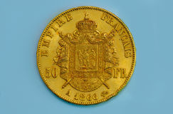 Old French gold coin. A 50 Francs gold coin from France isolated on a blue background royalty free stock photo